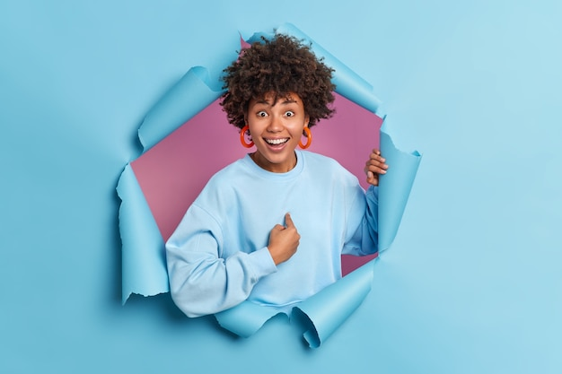Positive young afro american woman points at herself smiles broadly