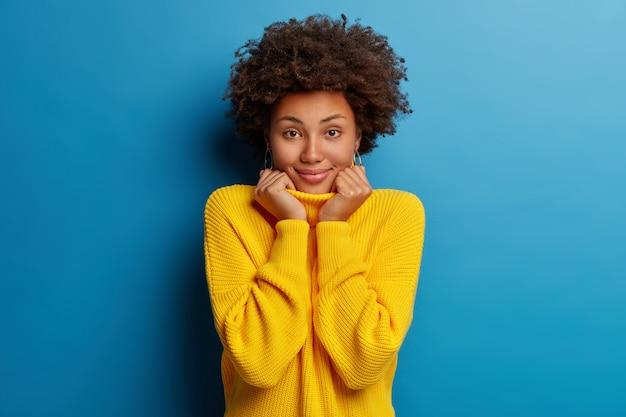 La giovane donna afroamericana positiva sorride ampiamente e indossa un maglione giallo isolato su sfondo blu.