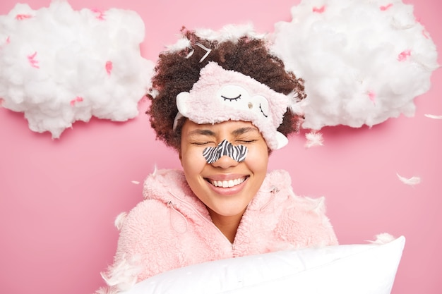 Positive young afro american woman smiles toothily keeps eyes closed enjoys morning time after good sleep wears slumber suit blindfold on forehead holds pillow poses against flying feathers
