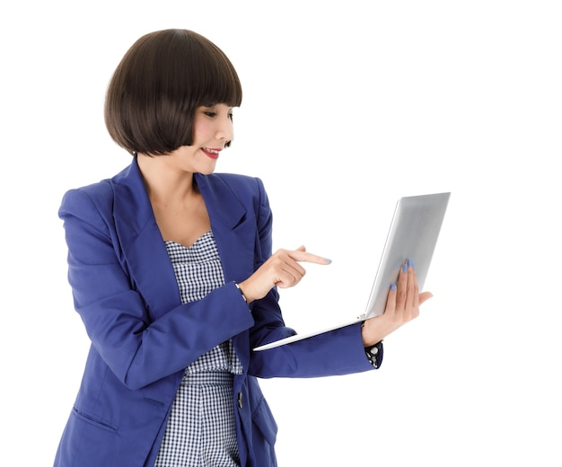 Positive young asian business lady in elegant blue clothes pointing at laptop screen and smiling while working online isolated on white background