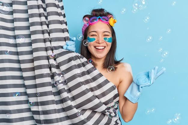 La giovane donna asiatica positiva applica cerotti di collagene idrogel sotto gli occhi, i bigodini si posano dietro la tenda della doccia e gode delle procedure igieniche