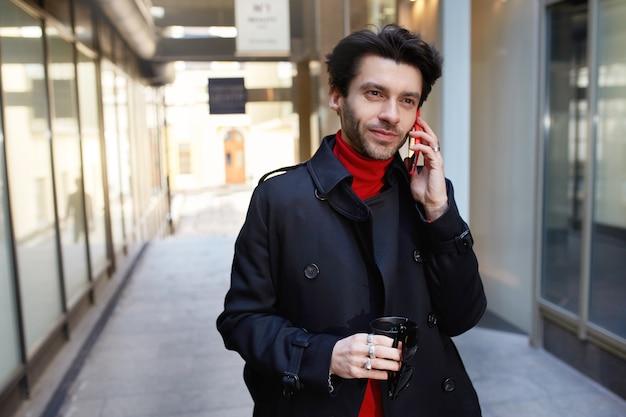 Positivo giovane attraente dai capelli castani maschio unshaved in abiti alla moda che tiene il caffè da asporto mentre si effettua una chiamata con il suo smartphone, camminando su sfondo di città