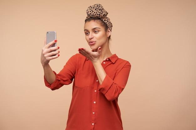 La giovane donna castana attraente positiva si è vestita in camicia rossa che piega le sue labbra e che tiene il palmo sollevato mentre soffia il bacio dell'aria nella parte anteriore, isolato sopra il muro beige