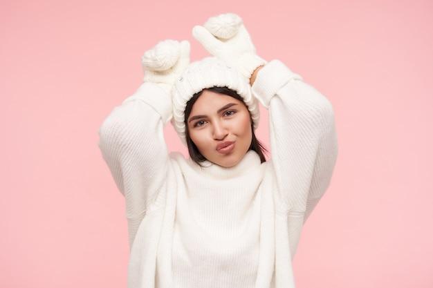 Позитивная молодая привлекательная брюнетка с распущенными волосами, поджав губы, делая смешные рожи и держа руки поднятыми, изолированная над розовой стеной
