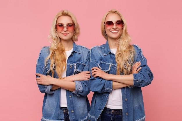 즐거운 미소로 카메라를보고 분홍색 배경 위에 서있는 동안 손을 유지하는 빨간 선글라스에 긍정적 인 젊은 매력적인 긴 머리 금발 여성