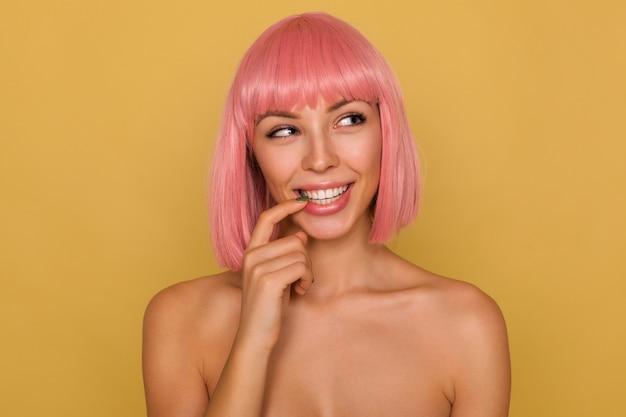 Позитивная молодая привлекательная розоволосая дама с короткой модной стрижкой хитро смотрит в сторону и улыбается, трогая нижнюю губу указательным пальцем, позируя над горчичной стеной