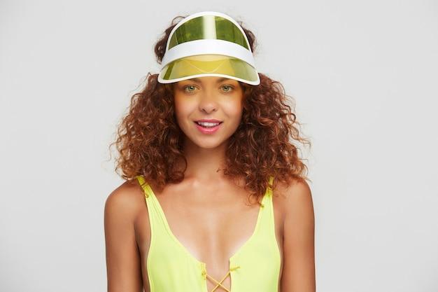 Positiva giovane femmina dai capelli rossi attraente con trucco naturale che sorride delicatamente mentre guarda la fotocamera, in piedi su sfondo bianco in costume da bagno giallo