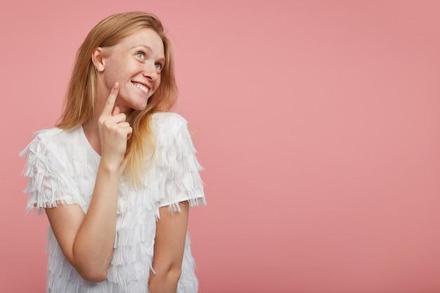 Signora rossa attraente giovane positiva mantenendo l'indice sulla guancia e guardando felicemente verso l'alto con un ampio sorriso, vestita con una maglietta bianca elegante mentre si trova su sfondo rosa