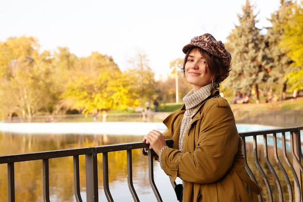 Positive young attractive short haired brunette female leaning on iron railing while posing over lake in city park, looking gladly  and smiling gently