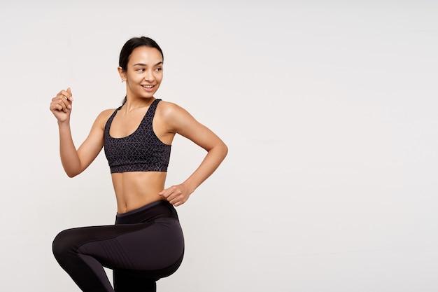 Позитивная молодая привлекательная спортивная брюнетка без макияжа, поднимающая руки, шагая и весело глядя через плечо, изолированная над белой стеной