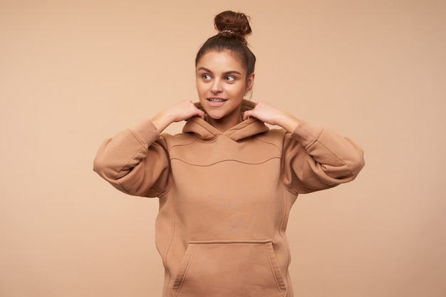 Positive young attractive woman wearing her brown hair in knot while standing over beige wall, looking aside with light smile and raising hands to her hood