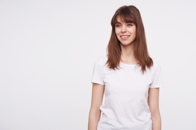 Positive young attractive woman with natural makeup looking cheerfully aside with pleasant smile, keeping hands along body while standing over white wall