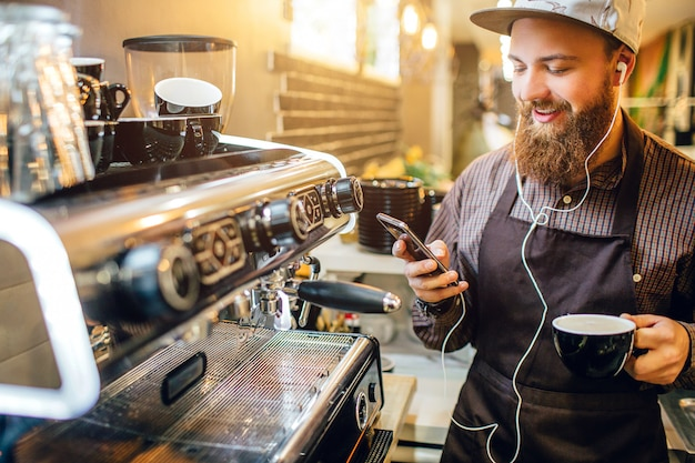 Positive young barista listen to music through earphones
