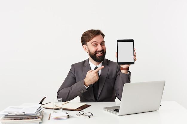 タブレットpcを手に白い壁の上のテーブルに座って、灰色のスーツを着て、広い笑顔で正面を向いている短いヘアカットのポジティブな若いひげを生やしたブルネットの男