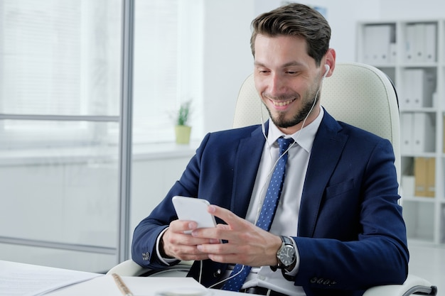 オフィスの椅子に座って、音楽を聴きながら電話をチェックするイヤホンでポジティブな若いひげを生やしたビジネスマン