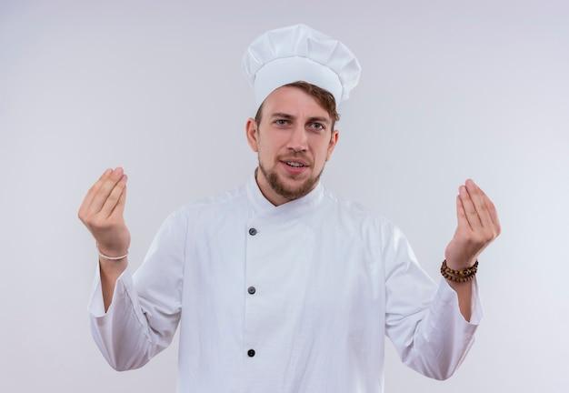 Un giovane uomo barbuto positivo del cuoco unico che indossa l'uniforme bianca del fornello e il cappello che tengono insieme le dita insieme il gesto della mano mentre osserva su una parete bianca