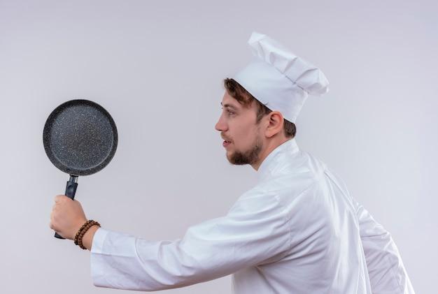 Un giovane uomo barbuto positivo del cuoco unico che indossa l'uniforme bianca del fornello e la padella della tenuta del cappello come una mazza da baseball su una parete bianca