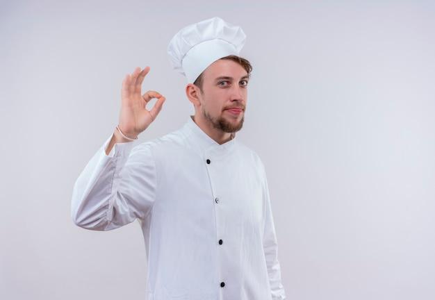 Un uomo barbuto giovane chef positivo in uniforme bianca che mostra gesto giusto su una parete bianca