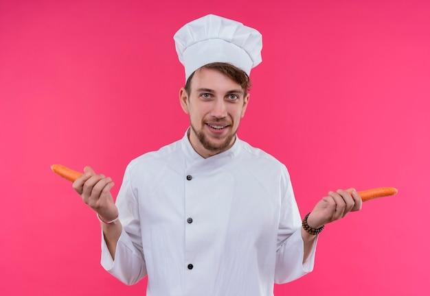 Un uomo barbuto giovane chef positivo in uniforme bianca che sorride e che tiene le carote mentre osserva su una parete rosa