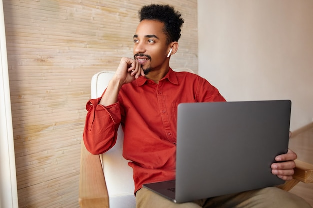 Positive young bearded dark skinned male with short haircut touching his face with raised hand and smiling slightly while looking at window, working remotely from home