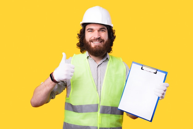 Positive young bearded engineer is holding his work   pappers  and looking at the camera is showing a thumb up