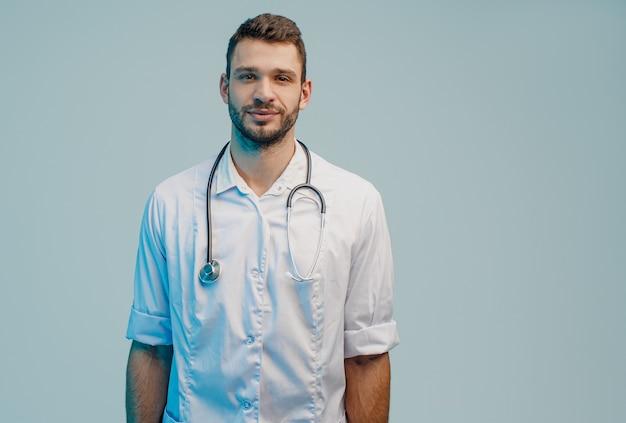 Положительный молодой бородатый европейский мужской портрет доктора. человек в белом халате со стетоскопом. изолированные на сером фоне с бирюзовым светом. студийная съемка. скопируйте пространство.