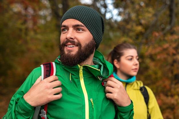 ガールフレンドと一緒に森をハイキング中に環境を探索しながら目をそらしている明るい緑のジャケットとニット帽のポジティブな若いひげを生やした男性のバックパッカー