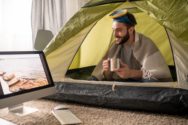 Positive young bearded man with diving mask on head drinking hot tea and contemplating seascape on computer monitor while travelling online