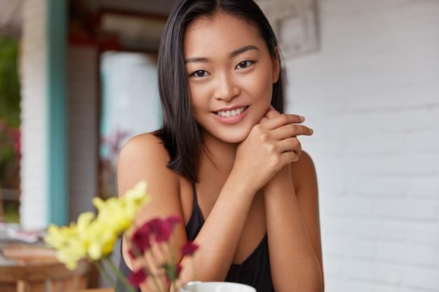 넓은 따뜻한 미소를 지닌 긍정적 인 젊은 아름다운 아시아 여성은 검은 머리카락과 건강한 피부를 가지고 있으며 레스토랑에서 좋은 휴식과 서비스에 만족합니다. 자연미