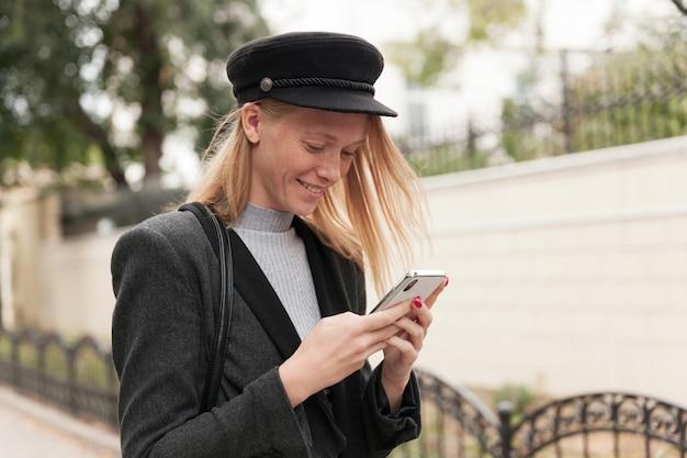 도시를 걷는 동안 유행의 옷을 입고 캐주얼 헤어 스타일을 가진 긍정적 인 젊은 아름다운 금발 여성, 제기 손에 휴대 전화를 들고 화면을 보면서 웃고