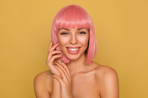 彼女の顔に手を上げて、マスタードの壁の上にポーズをとって、大きく笑っている間、彼女の白い完璧な歯を見せている短いピンクの髪を持つポジティブな若い美しい青い目の女性