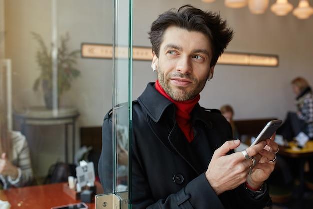 Positivo giovane bel ragazzo barbuto dai capelli castani mantenendo il telefono cellulare in mani alzate e guardando pensieroso nella finestra, in posa su sfondo di caffè