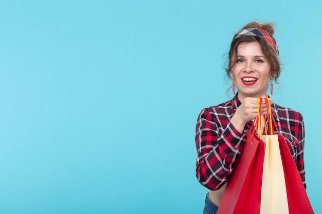 격자 무늬 셔츠에 긍정적 인 젊은 아름다운 여자와 복사 공간이 파란색 표면에 쇼핑백을 들고