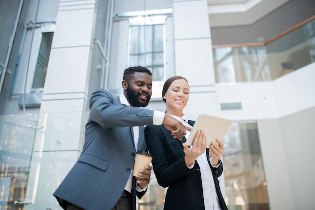 女性の同僚とオンラインプロジェクトの実装について話し合っている間、タブレット画面を指しているポジティブな若い黒人ビジネスマン