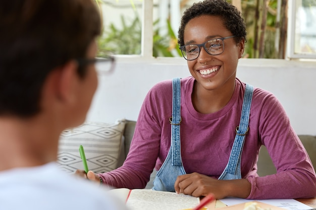 Positive young black female journalist in spectacles