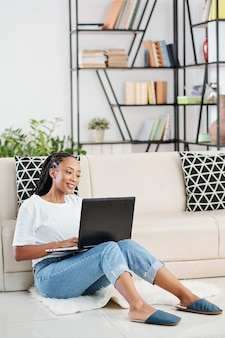 Positive young black woman with dreadlocks sitting on the floor in living room and coding on laptop