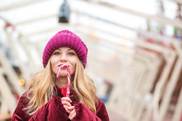 通りでキャンディケインとポーズをとって赤いニット帽のポジティブな若いブロンドの女性