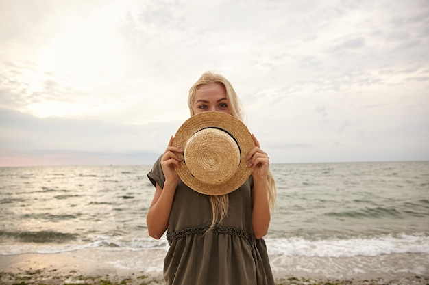Positive young blue-eyed attractive white-headed female keeping her boat hat in front of herself while looking gladly at camera, isolated over beach background