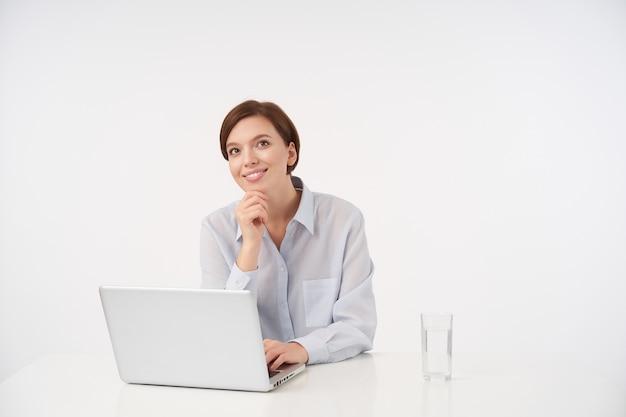 Позитивная молодая кареглазая брюнетка с непринужденной прической держит руку на подбородке и весело смотрит в сторону с очаровательной улыбкой, сидя на белом