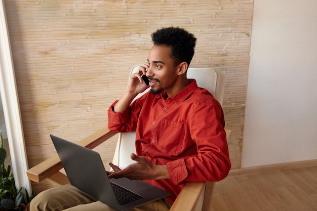 家のインテリアの椅子に座って少し笑っている間彼のスマートフォンで電話をかけるトレンディな短いヘアカットを持つポジティブな若いブルネットのひげを生やした暗い肌の男