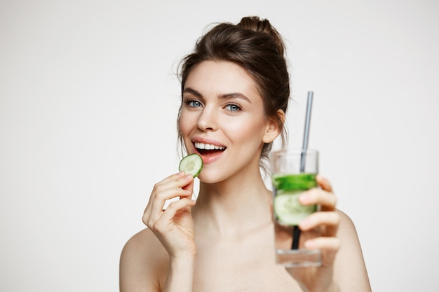 Giovane ragazza castana positiva che sorride esaminando macchina fotografica che mangia la fetta del cetriolo che tiene bicchiere d'acqua sopra fondo bianco. bellezza e salute.