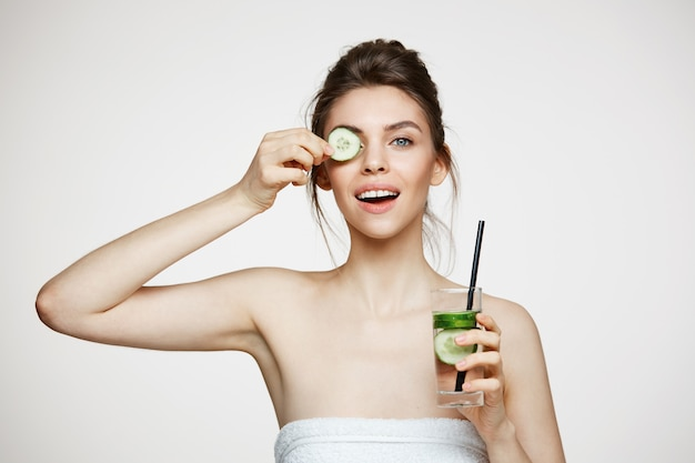 Positive young brunette girl smiling looking at camera holding cucumber slice holding glass of water over white background. beauty and health.