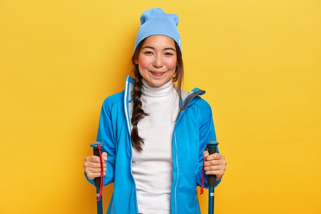 Positive young brunette woman enjoys nordic walking, holds trekking sticks, trains on forest trail, wears blue hat, jacket and white turtleneck, poses against yellow background. hiking and camping