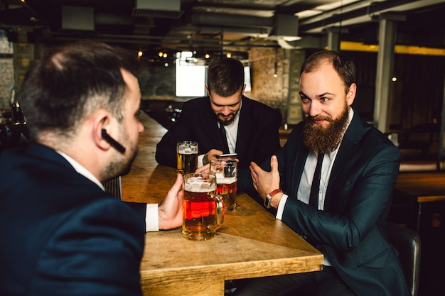Positive young bsinessmen in suits sit together at table. they hold mugs of beer. guy in front has balck headphone in ear. men are in bar.