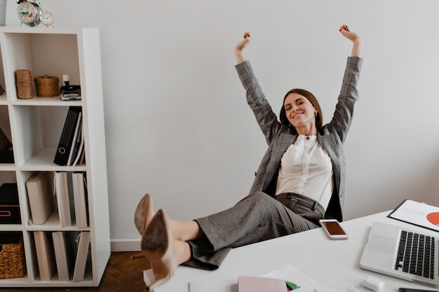 Positive young business lady leans back in her chair and raises her arms up with satisfaction against shelves of documents.