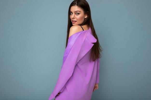 Позитивный молодой бизнес длинные волосы брюнетка женщина в фиолетовом костюме изолирована на синем