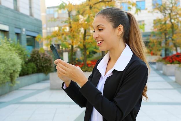 都市の背景を持つ彼女のスマートフォンアプリで写真を送信する肯定的な若いビジネス女性。