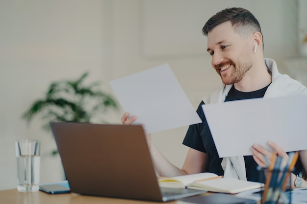Positive young businessman in casual wear analyzing project results and feeling happy, using modern laptop at his cozy workplace at home. successful entrepreneur feeling satisfied with business result