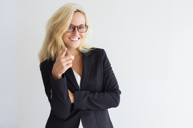 Positive young businesswoman pointing at camera