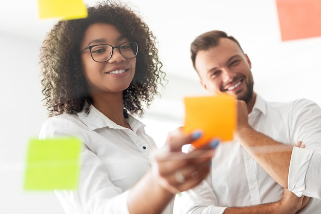 Positive young businesswoman putting sticky note on glass wall while standing next to cheerful male colleague and together discussing project brainstorming and making decision